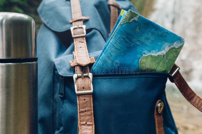 Hipsterblåttryggsäck, översikt och termosCloseup Sikt från Front Tourist Traveler Bag On vattenfallbakgrund Högt resaaffärsföreta arkivfoton