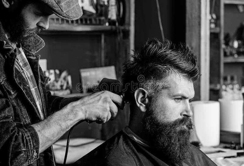 Hipstercliënt die kapsel krijgen De kapper met haarclipper werkt aan kapsel voor de mens met baard, herenkapperachtergrond stock afbeeldingen