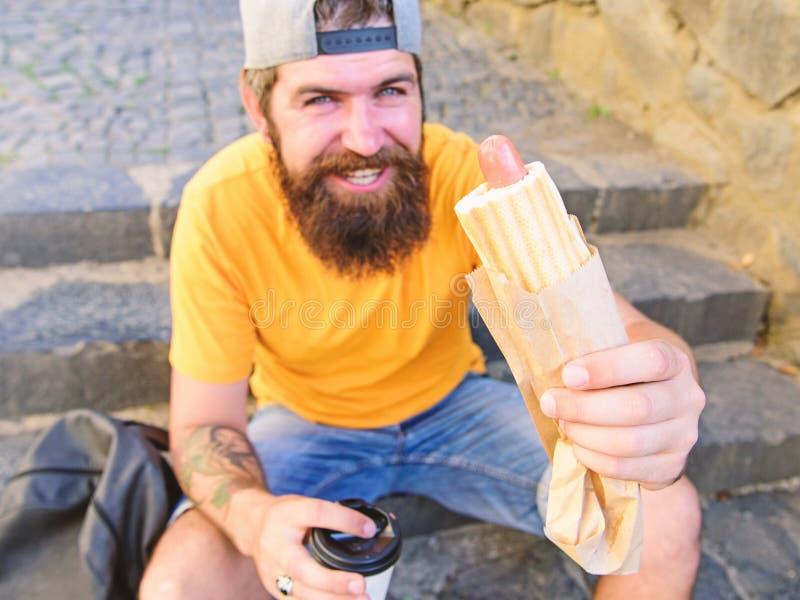 Hipsteren äter varmkorven, medan sitt på trappa utomhus Tyck om ditt målbegrepp Tycker om den skäggiga hipsteren för mannen stads royaltyfria foton