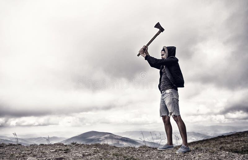 Hipsteren med sk?gget rymmer yxan medan st?llningen ?verst av berget, himmel p? bakgrund, kopieringsutrymme Brutal skogsarbetare  arkivbild