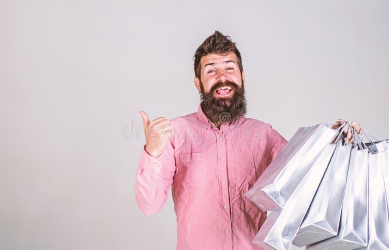 Hipsteren p? att le framsidan rekommenderar att k?pa Mannen med sk?gget och mustaschen b?r gruppen av shoppingp?sar, gr? bakgrund royaltyfri fotografi