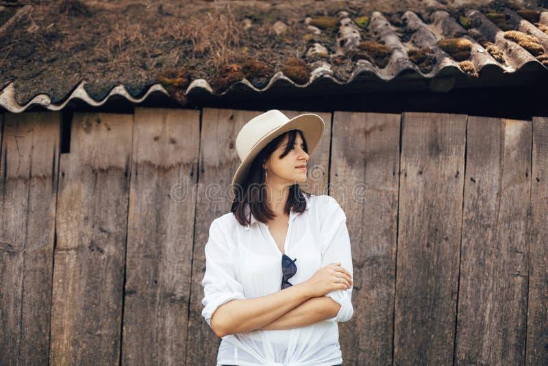 Hipsterflicka i den vita tillfälliga dräkten som poserar på bakgrund av den gamla träkabinen i berg Stilfull kvinna i hatten som  arkivbilder