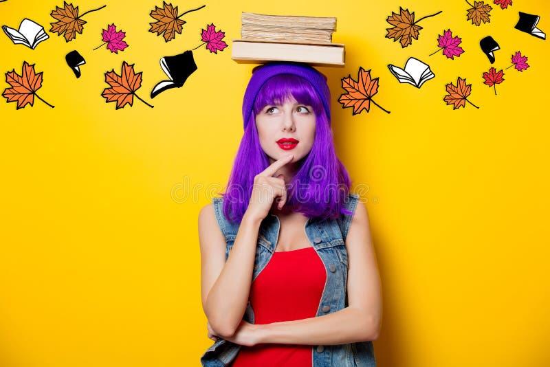 Hipsterflicka med den purpurfärgade frisyren med böcker royaltyfri bild