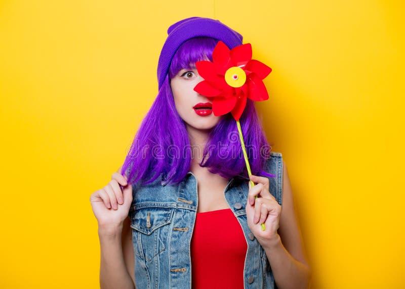 Hipsterflicka med den purpurfärgade frisyren med lilla solen arkivbild