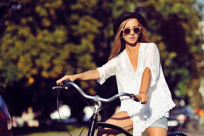 Hipsterflicka på en tappningcykel - utomhus- modestående arkivfoton