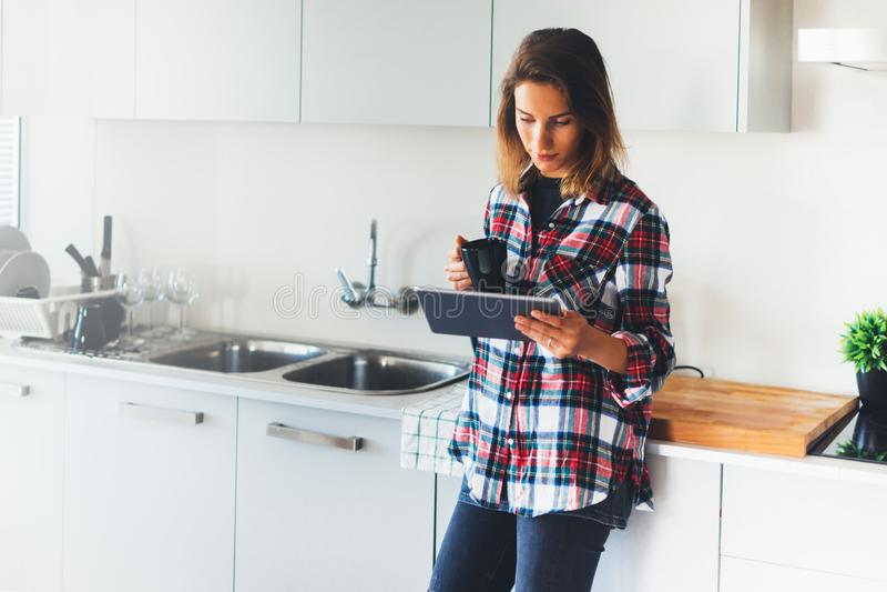 Hipsterflicka som använder minnestavlateknologi- och drinkkaffe i kök, arkivfoto