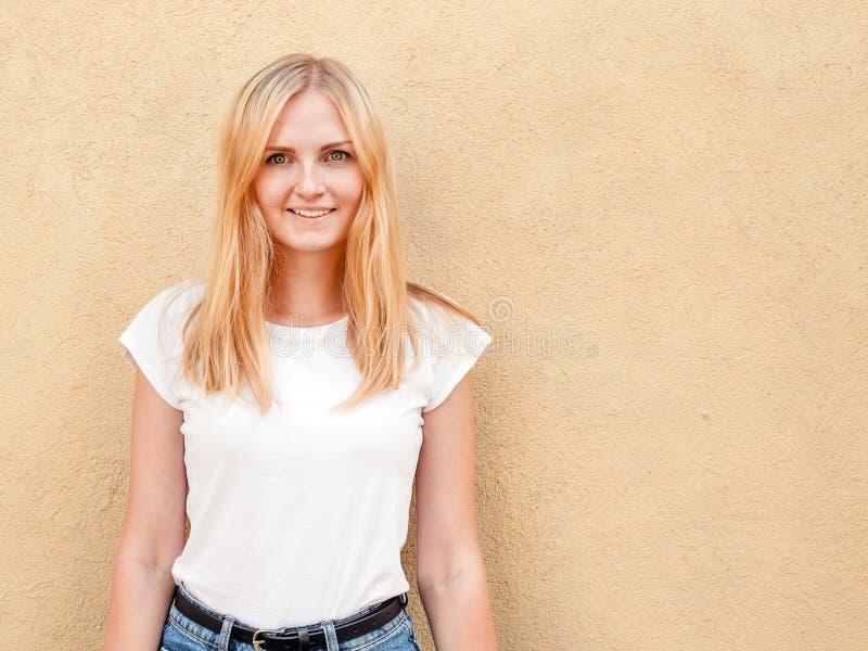 Hipsterflicka som bär den tomma vita t-skjortan och jeans som poserar mot den grova gataväggen, minimalist stads- klädstil arkivbilder