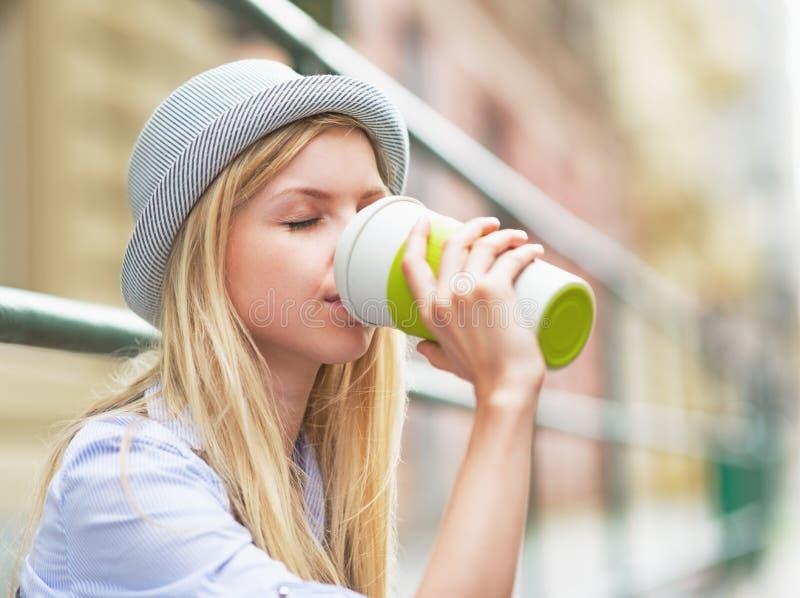 Hipsterflicka som dricker den varma drycken på stadsgatan royaltyfri bild