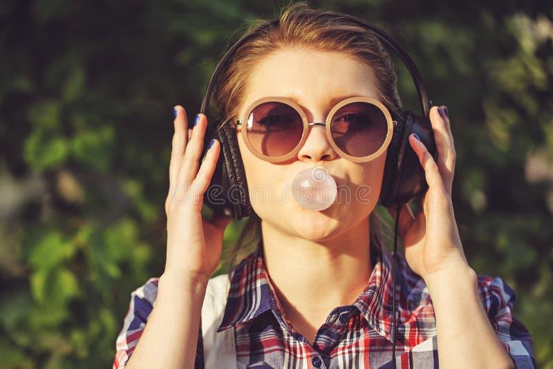 Hipsterflicka som lyssnar till musik på hörlurar och tuggningar bollen av idisslad föda royaltyfri foto