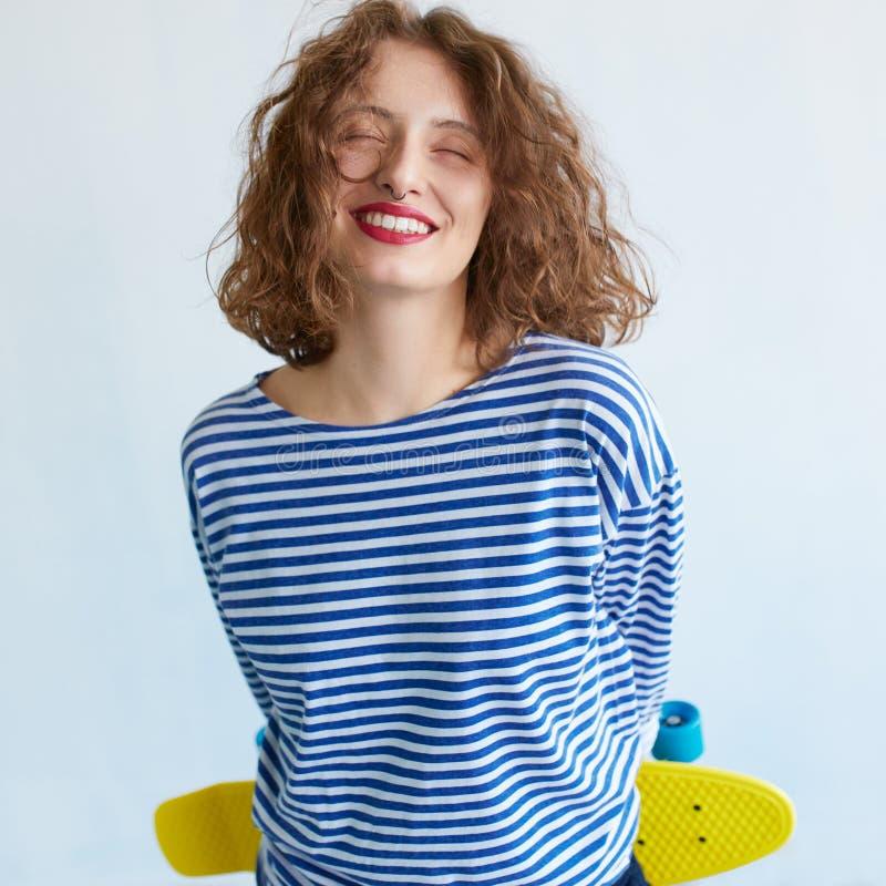Hipsterflicka som rymmer en livlig färgskateboard arkivfoton