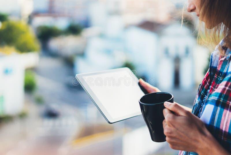 Hipsterflickan som använder minnestavlateknologi- och drinkkaffe, hållande dator för flickaperson på bakgrund Sun City, kvinnlig  royaltyfria foton