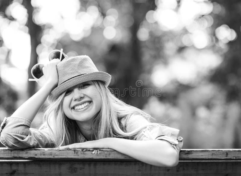 Hipsterflickasammanträde på bänk i parkera royaltyfri fotografi