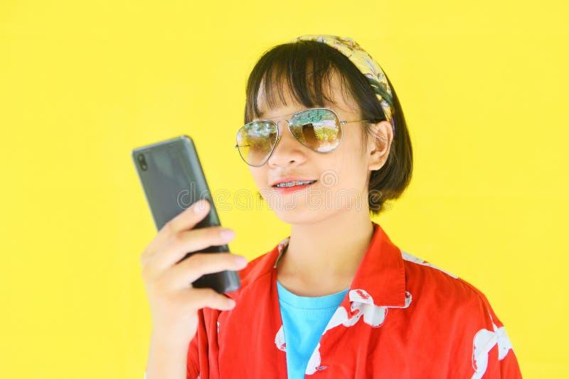 Hipsterflickastående av angenämt älskvärt kort hår med exponeringsglas och lyckligt ungt asiatiskt tonårigt flickamode för rymma  arkivbilder