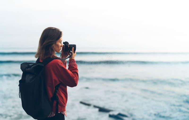 Hipsterfotvandrareturist med ryggsäcken som tar fotoet av den fantastiska seascapesolnedgången på kamera på bakgrundsblåtthavet,  royaltyfria foton
