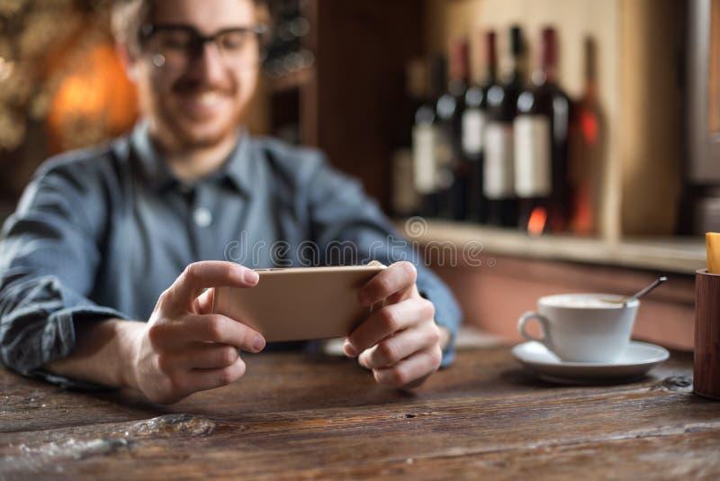 Hipstergrabb på restaurangen genom att använda en mobiltelefon arkivbild