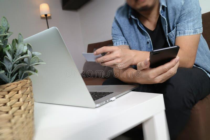 hipsterhand genom att använda smart telefon- och bärbar datorcompter, hållande cradit arkivfoton