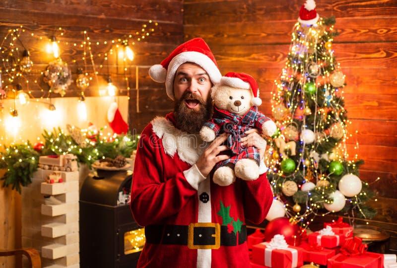 Hipsterkerstman thuis Gebaarde mens die pret hebben dichtbij Kerstboom binnen De atmosfeer van huiskerstmis Mensen in de winter royalty-vrije stock afbeelding