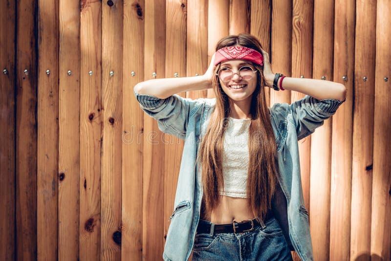 Hipsterkvinna nära träbakgrund royaltyfri foto