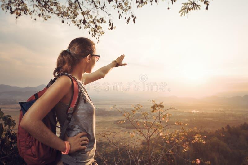 Hipsterkvinnahandelsresande med ryggsäcken som tycker om sikt av solnedgången arkivfoton