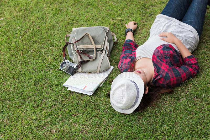Hipsterkvinnahandelsresande som ligger på gräset royaltyfri bild
