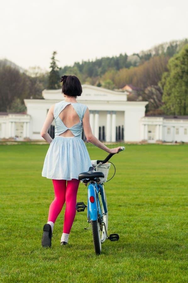 Hipsterkvinnan som går sidan - förbi - sid med en cykel royaltyfri bild