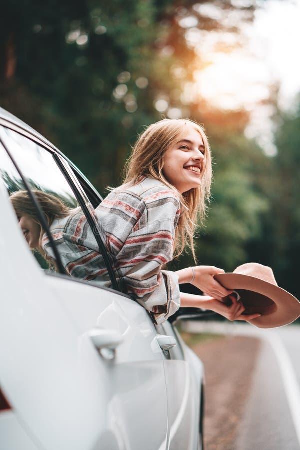 Hipsterkvinnaresande med bilen på den lösa skogvägen Den stiliga lyckliga flickan som bär den rutiga skjortan och hatten, sitter  arkivbild