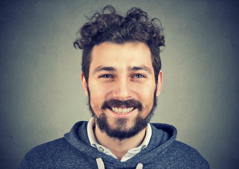 Hipsterman i grå hoodie som lyckligt ler på kameran royaltyfri foto
