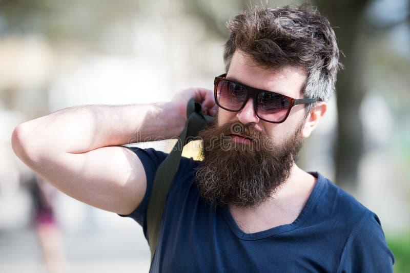 Hipsterman med det stilfulla skägget och mustasch som går i stad Closeupstående av den stiliga unga mannen i moderiktig eyewear arkivbild