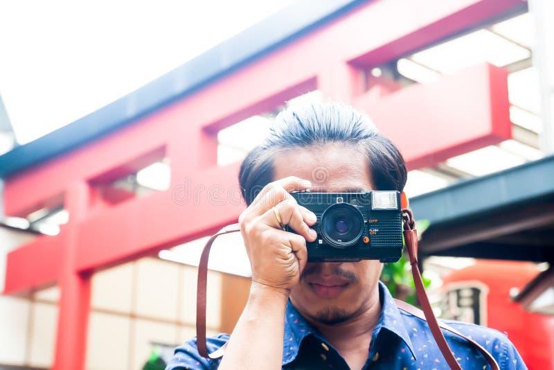 Hipsterman med en kamera i staden av Japan Resor Tappning arkivbild
