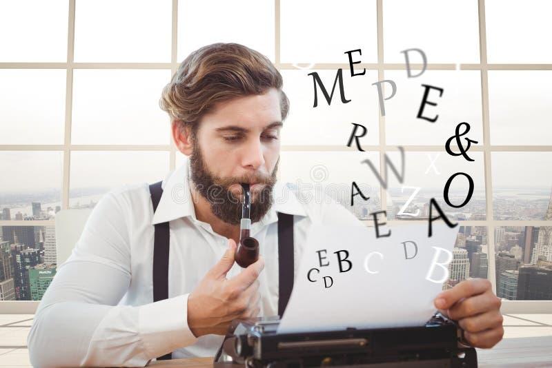 Hipsterman med ett rör som framme reflekterar på hans skrivmaskin av havsbakgrund arkivbilder