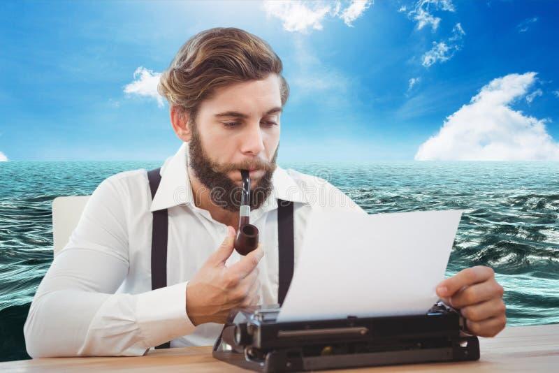 Hipsterman med ett rör som framme reflekterar på hans skrivmaskin av havsbakgrund royaltyfri bild