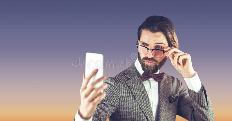 Hipsterman med exponeringsglas som tar en selfie på blå bakgrund royaltyfria bilder