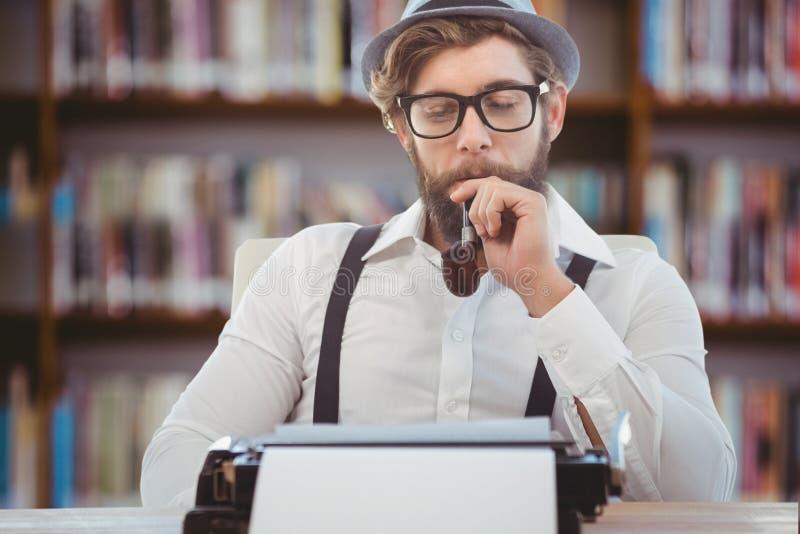 Hipsterman med hatten, röret och exponeringsglas som reflekterar på hans skrivmaskin royaltyfri fotografi