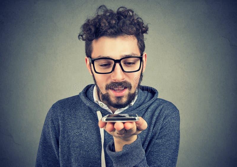 Hipsterman som använder en smart funktion för telefonstämmaerkännande fotografering för bildbyråer