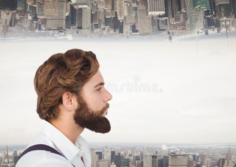 Hipsterman som långt borta ser med staden som bakgrund arkivbild