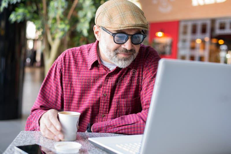 Hipsterman som offentligt använder stället för dator arkivbilder