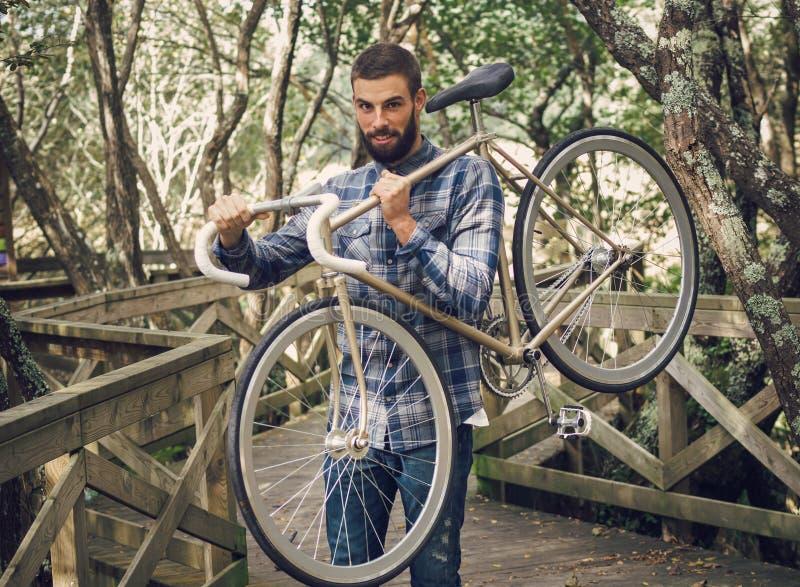 Hipsterman som rymmer hans cykel fotografering för bildbyråer