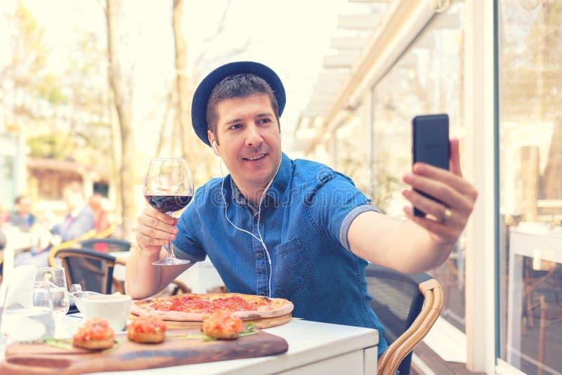 Hipsterman som sitter på tabellen med stor pizza, och bruschetta som rymmer exponeringsglas av rött vin som tar selfie royaltyfri fotografi