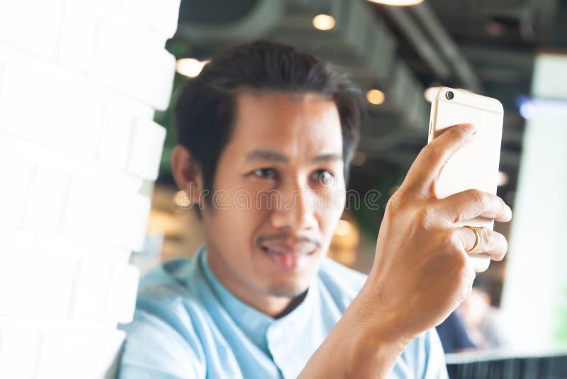 Hipsterman som stannar till framsidatid genom att använda smartphonen Smart liv- och teknologibegrepp Fokus p? smartphonen fotografering för bildbyråer