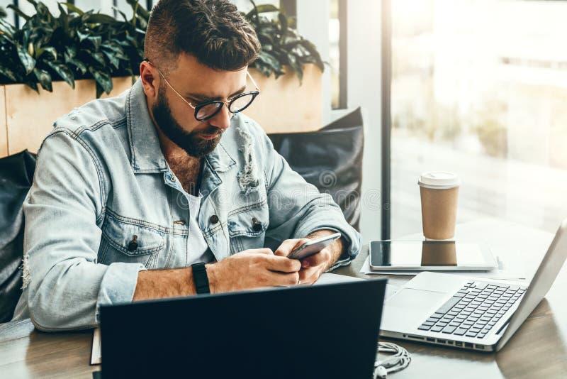 Hipstermannen sitter i kafé, använder smartphonen, arbetar på två bärbara datorer Affärsmannen läser ett informationsmeddelande i royaltyfri bild