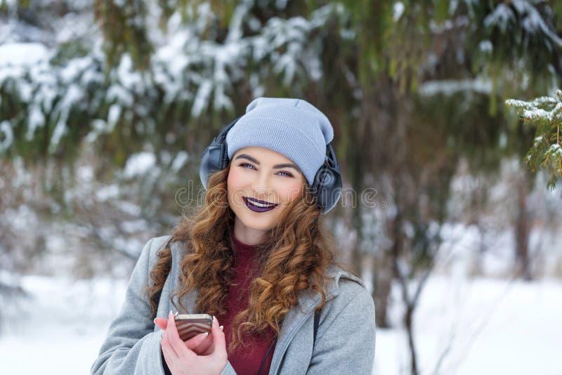 Hipstermeisje die aan muziek in de winter luisteren royalty-vrije stock foto