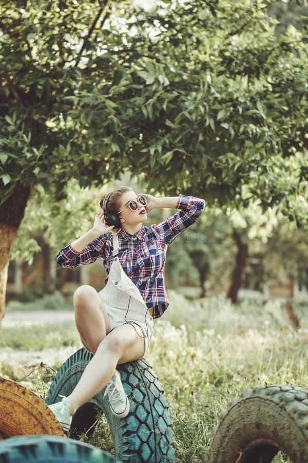 Hipstermeisje die aan muziek met hoofdtelefoons in de zomerpark luisteren royalty-vrije stock fotografie