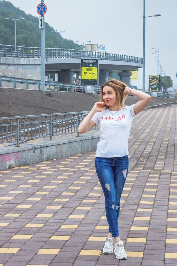 Hipstermeisje die lege witte t-shirt, jeans en honkbal GLB het stellen tegen ruwe straatmuur, volledig lengteportret dragen, stock foto