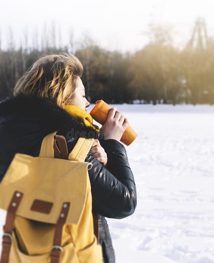 Hipstermeisje die met gele rugzak hete thee of koffie op achtergrond van de winterbos in de sneeuwbergen drinken Wandelende toeri stock foto's