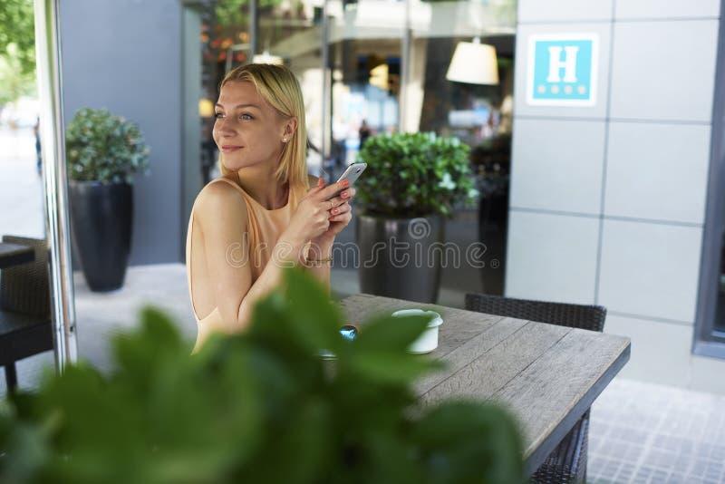 Hipstermeisje die op slimme telefoon in de winkelterras van de stoepkoffie babbelen stock afbeelding