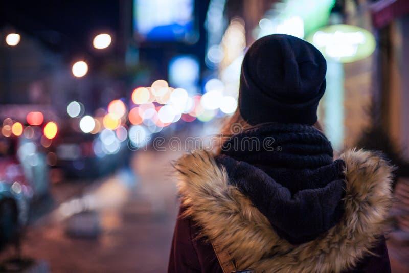 Hipstermeisje die op stadsstraat bij nacht lopen royalty-vrije stock foto