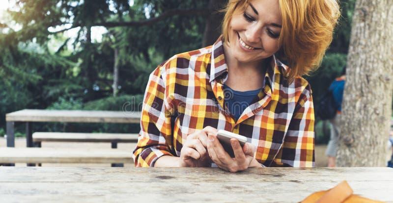 Hipstermeisje die telefoontechnologie Internet gebruiken, blogger persoon die mobiele smartphone op achtergrondzonstad houden, vr stock afbeeldingen