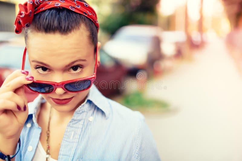 Hipstermeisje die zonnebril en maniertoebehoren dragen Glimlachend meisje die grappige gezichten in levensstijlportret maken stock foto's