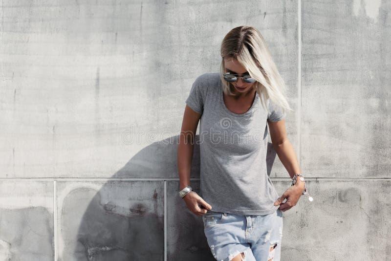 Hipstermeisje in grijze t-shirt over straatmuur royalty-vrije stock afbeeldingen