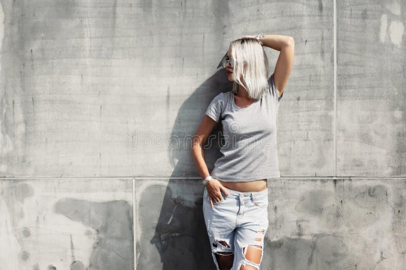 Hipstermeisje in grijze t-shirt over straatmuur royalty-vrije stock foto's